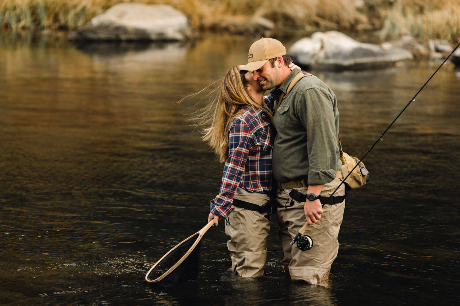 Fly fishing couple; woman holds net, leans in for a whisper in fiances ear.