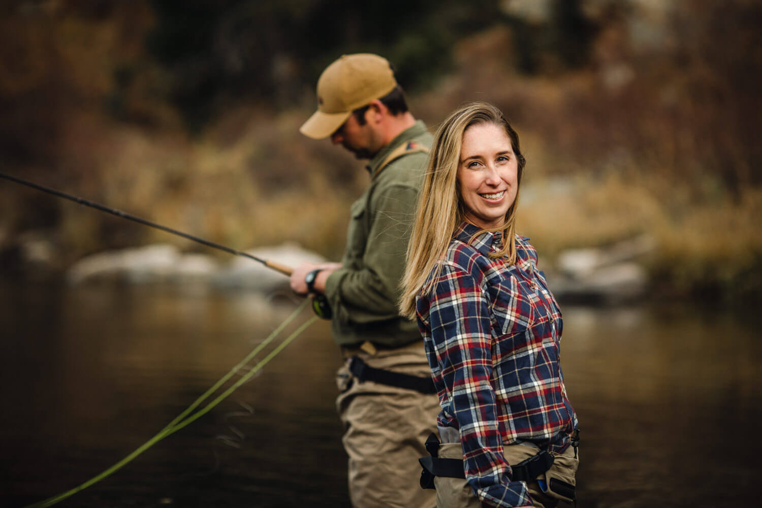 Woman in plaid shirt smiles at camera. Man fishes.
