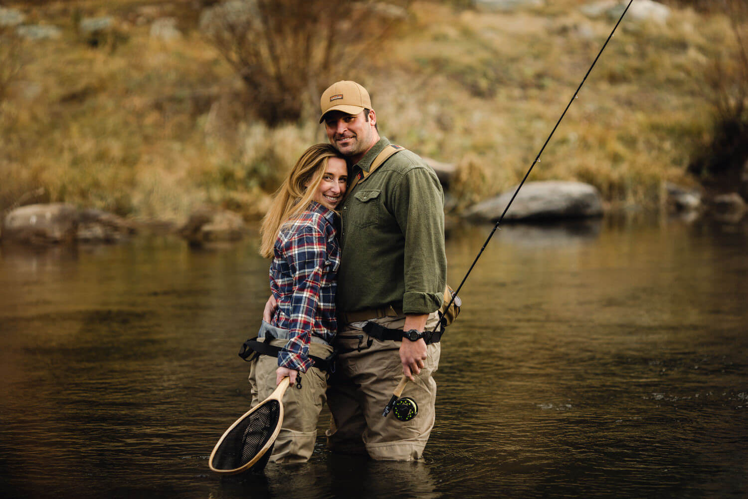 Couple in river fishing. Woman leans in for a hug.
