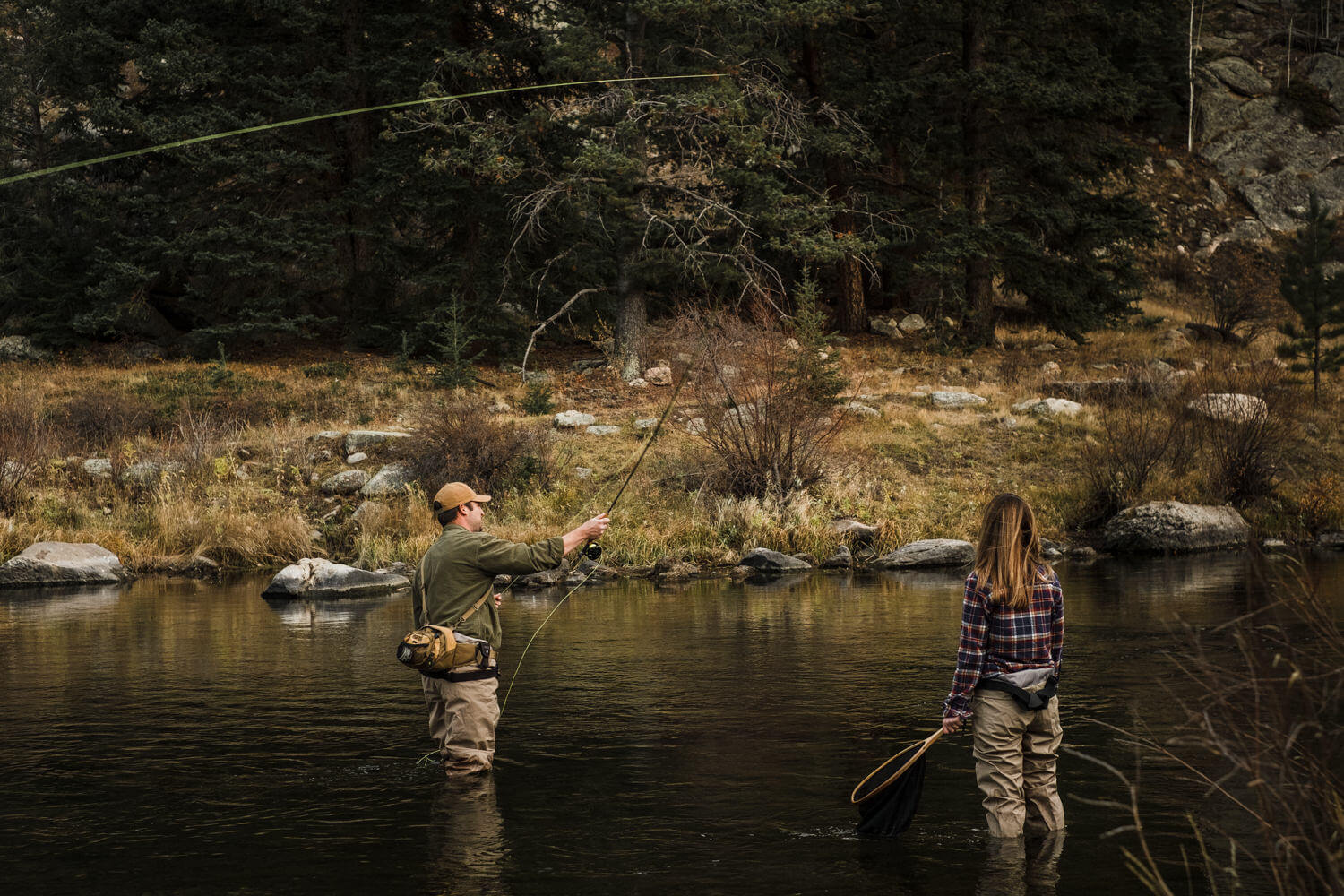 Man and woman in plaid shirts fly fish.