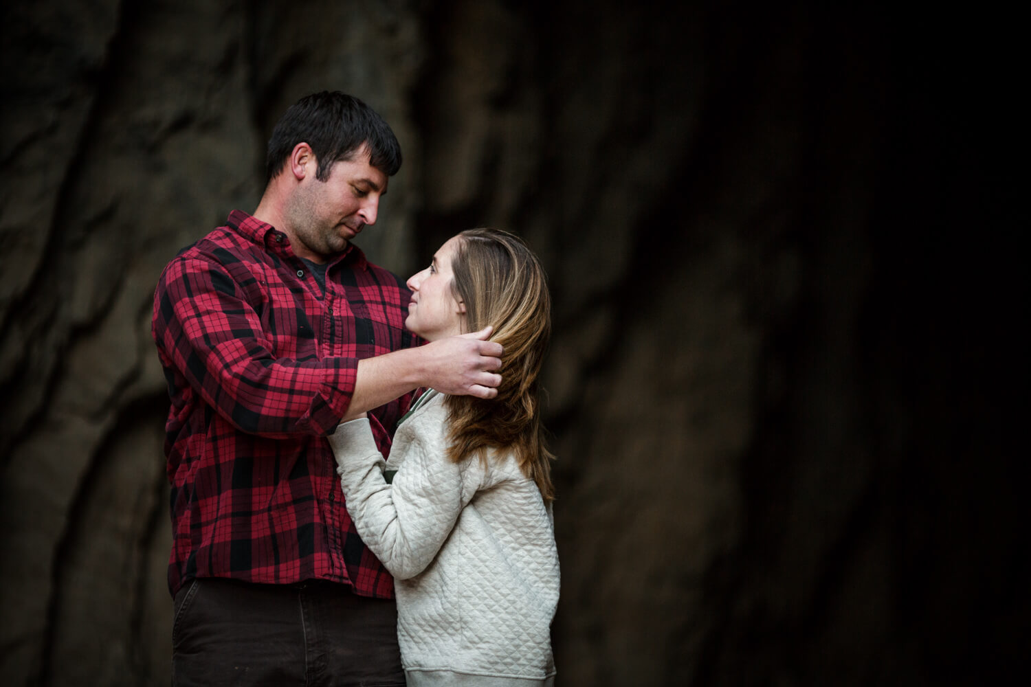 Couple embracing. Man in red flannel shirt, woman in patagonia fleece with rock bridge in background.