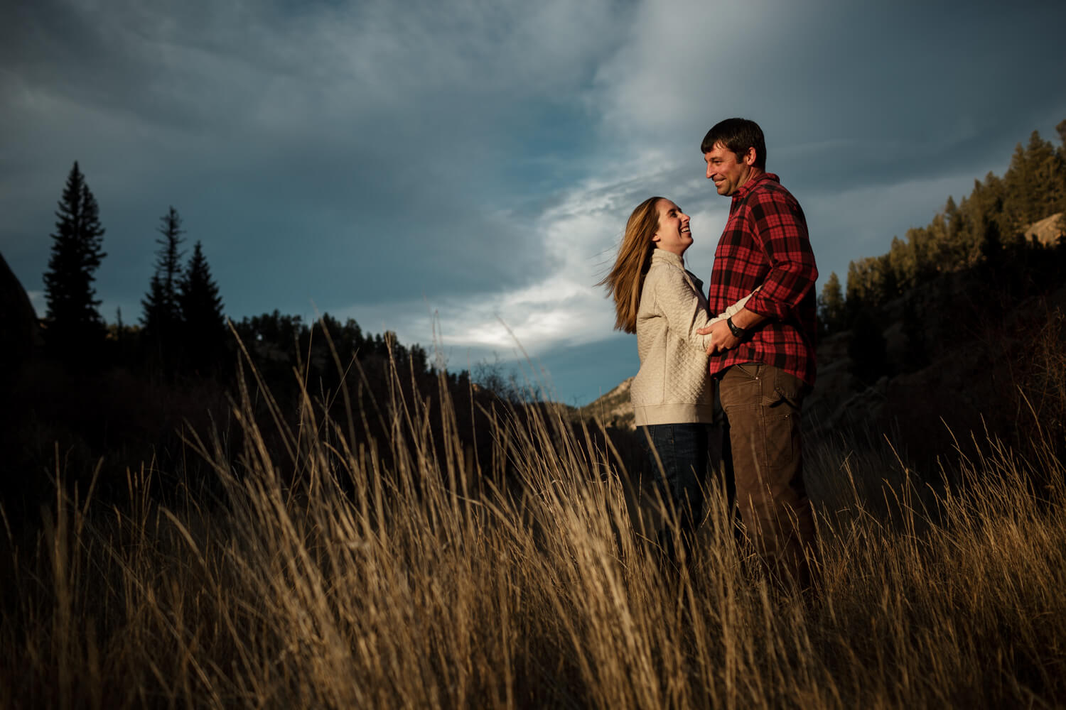 Setting sun illuminates a cute, outdoorsy engaged couple.