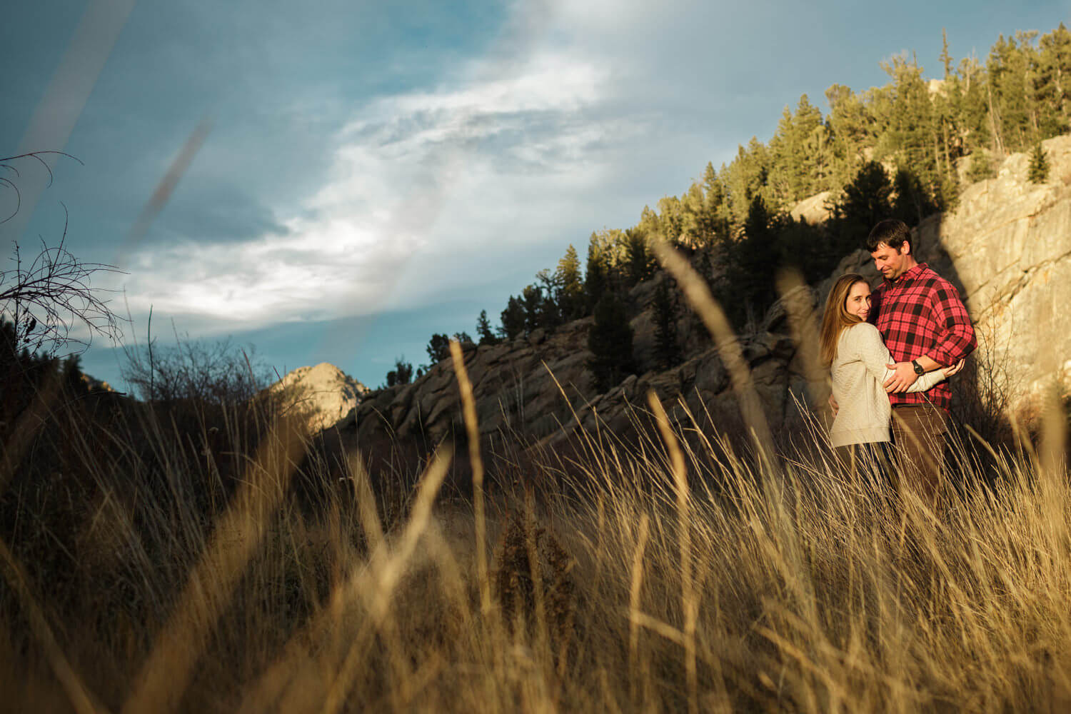 Golden hour with an engaged couple standing in the golden grass in the distance.