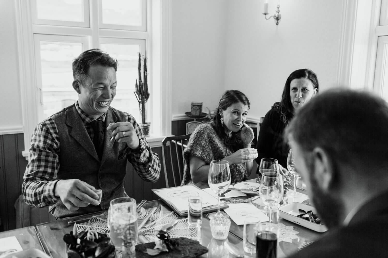 Black and white image of couple at dinner table, laughing and making face full of emotion.