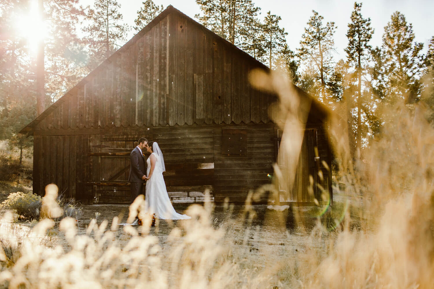 Evening light at Hollinshead Park. Bride and groom stand in front of barn.