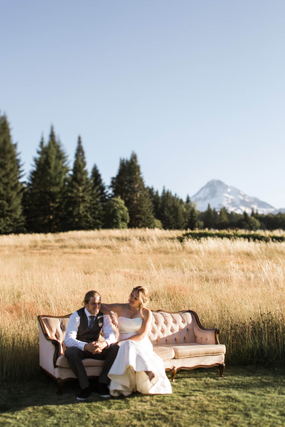 Young couple casually sits in golden sun light with Mt. Hood in the background.