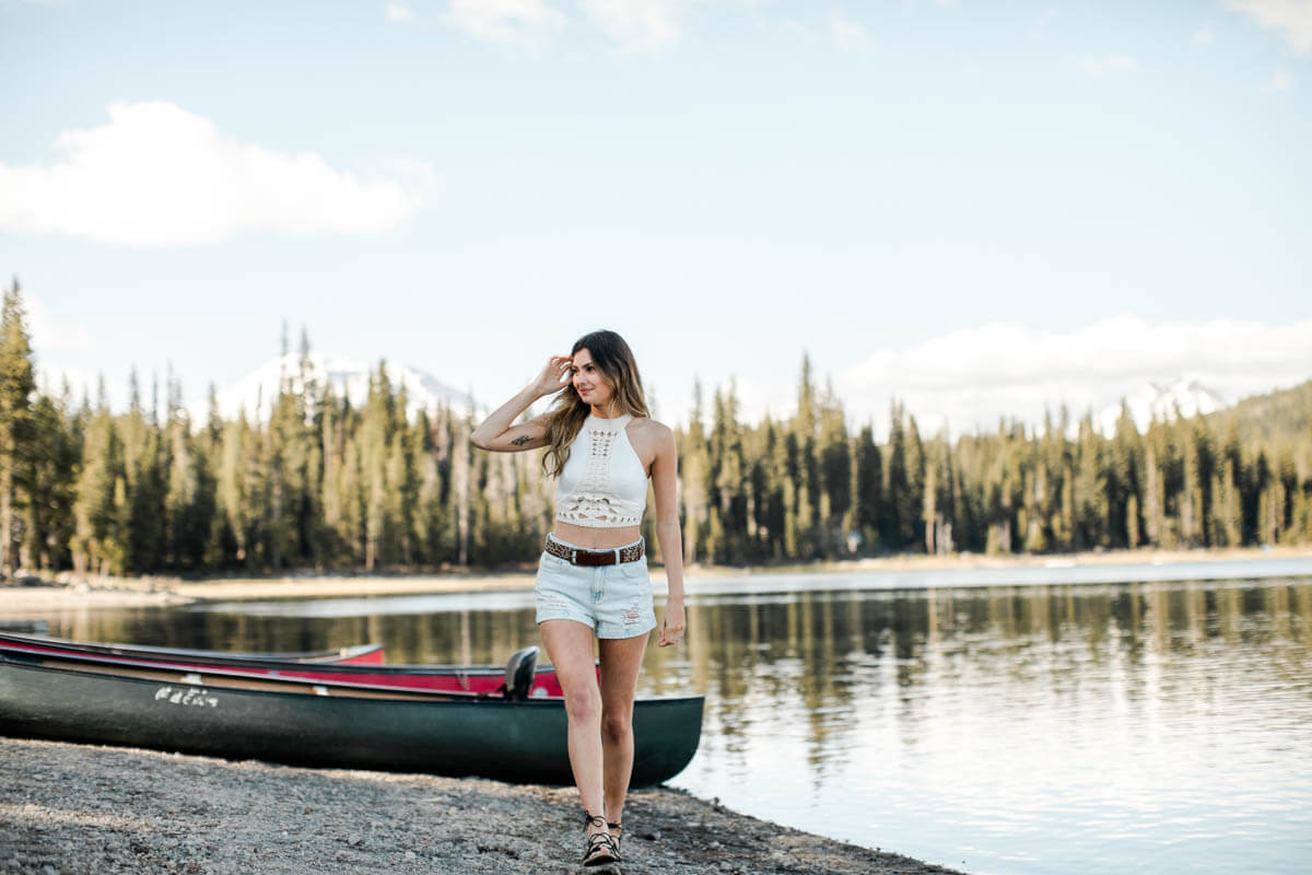 girl walking along lake, canoe in background