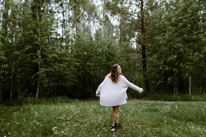 High school girl running in field of dandelions.