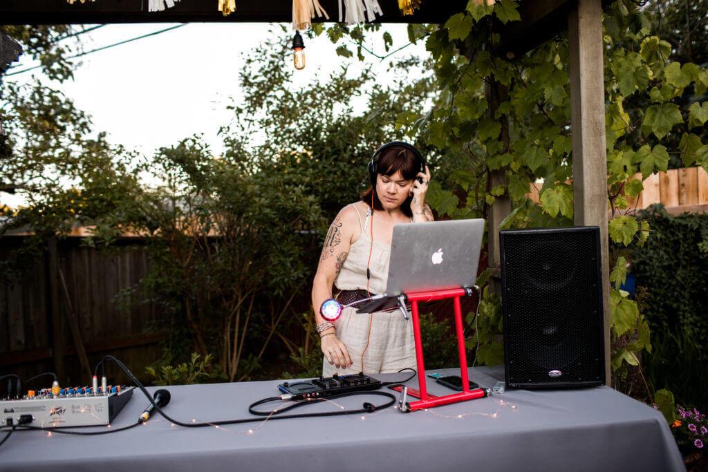 DJ Zia McCabe under garden arbor.