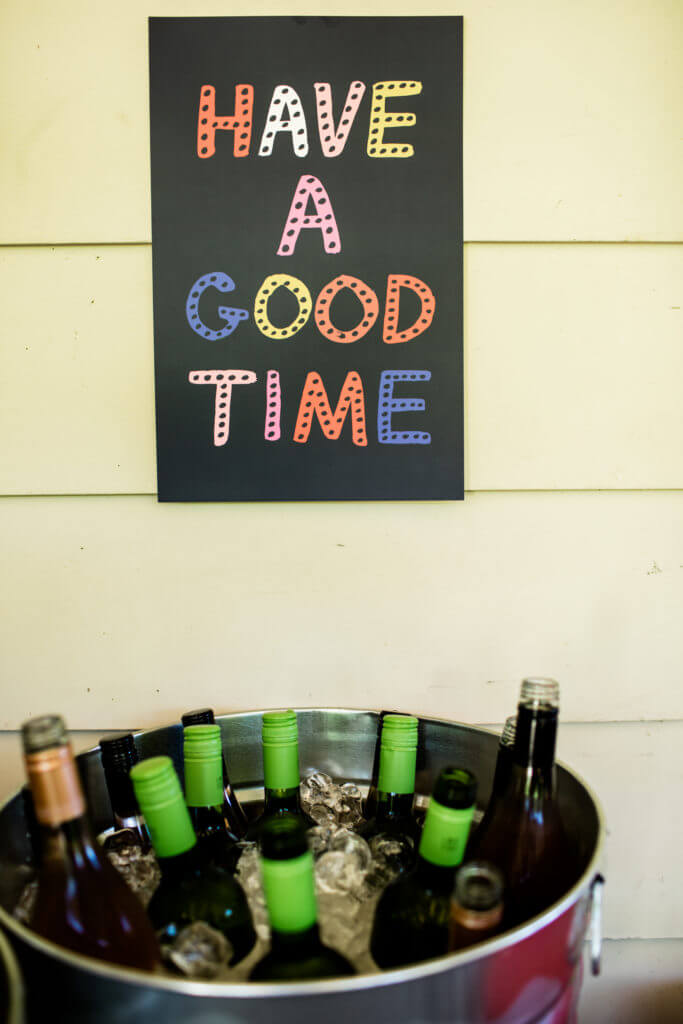 "Sign reads ""A good time"" above bottles of wine in ice."