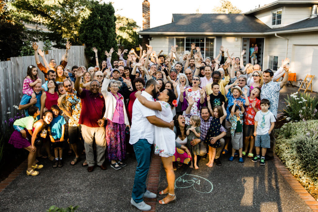 Group photo of party guests. Couple kisses in front of house.