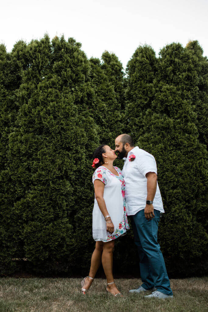 Couple kisses in backyard in front of hedge.