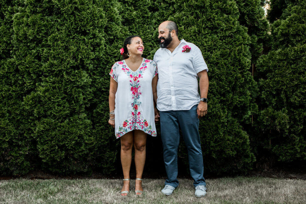 Couple stands next to each other smiling. Standing in front of hedge.