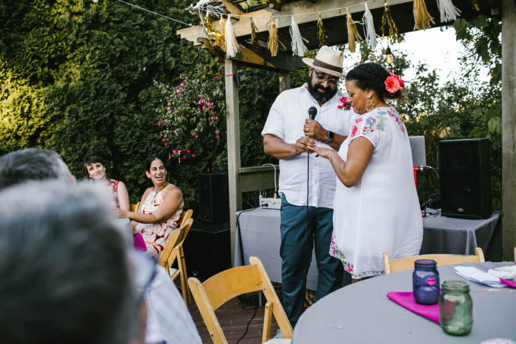 Couple reads each other vows at backyard anniversary party.