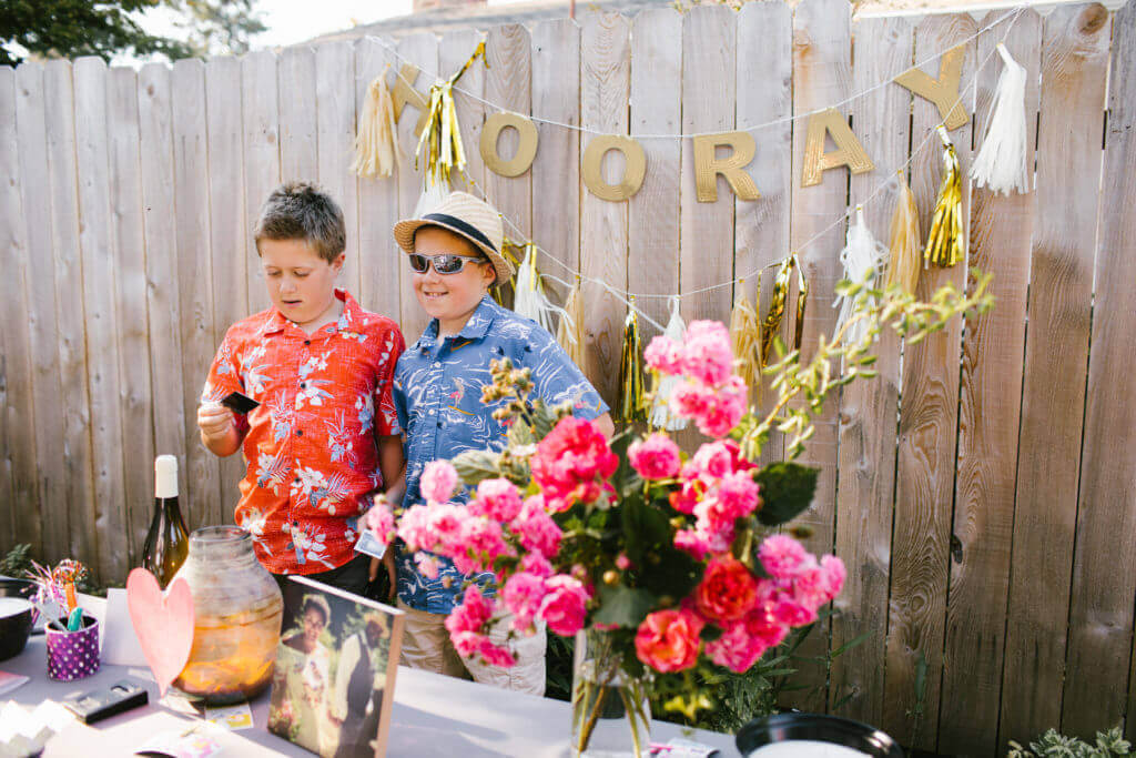 Two young boys stand at picture and gift table.