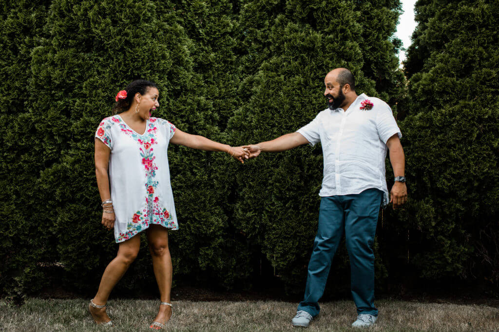 Couple holds hands playfully in front of hedge.