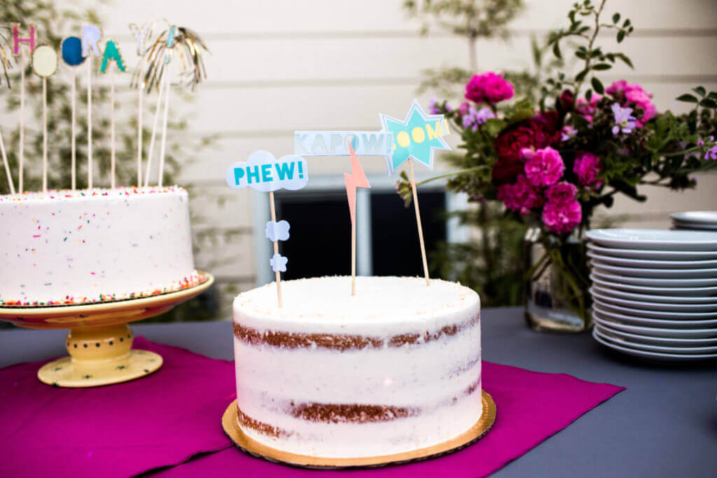 white cake with bright lettering as decor.