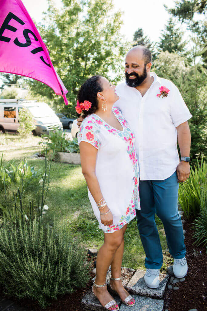 Couple stands in front yard with pink 'resist' sign.