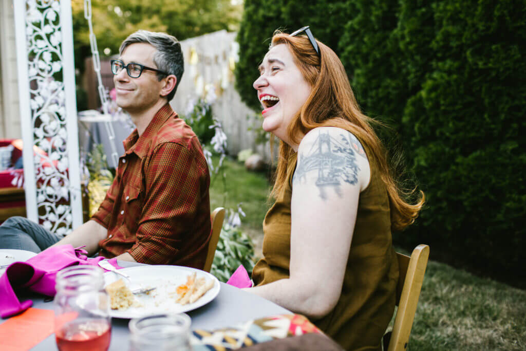 Red haired woman laughs while sitting next to grey haired man at backyard table.