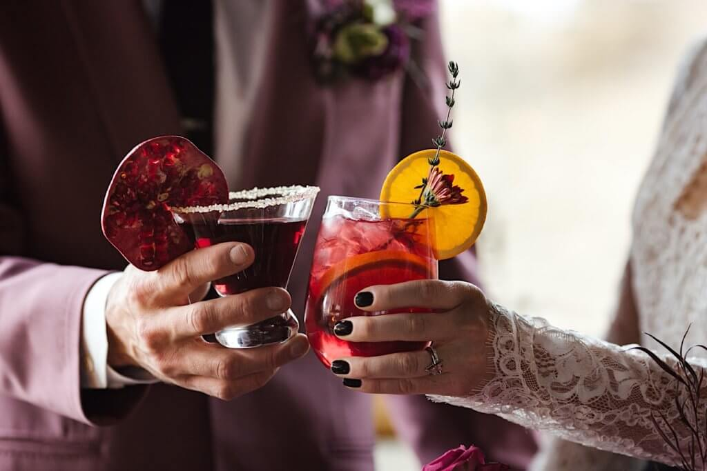 Close-up of bride and groom toasting with cocktails.