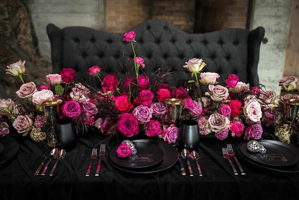 Reception table with pink roses, matte black and chrome details.