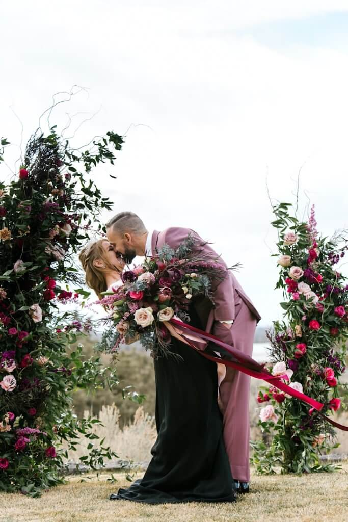 Emotional kiss surrounded by flowers.