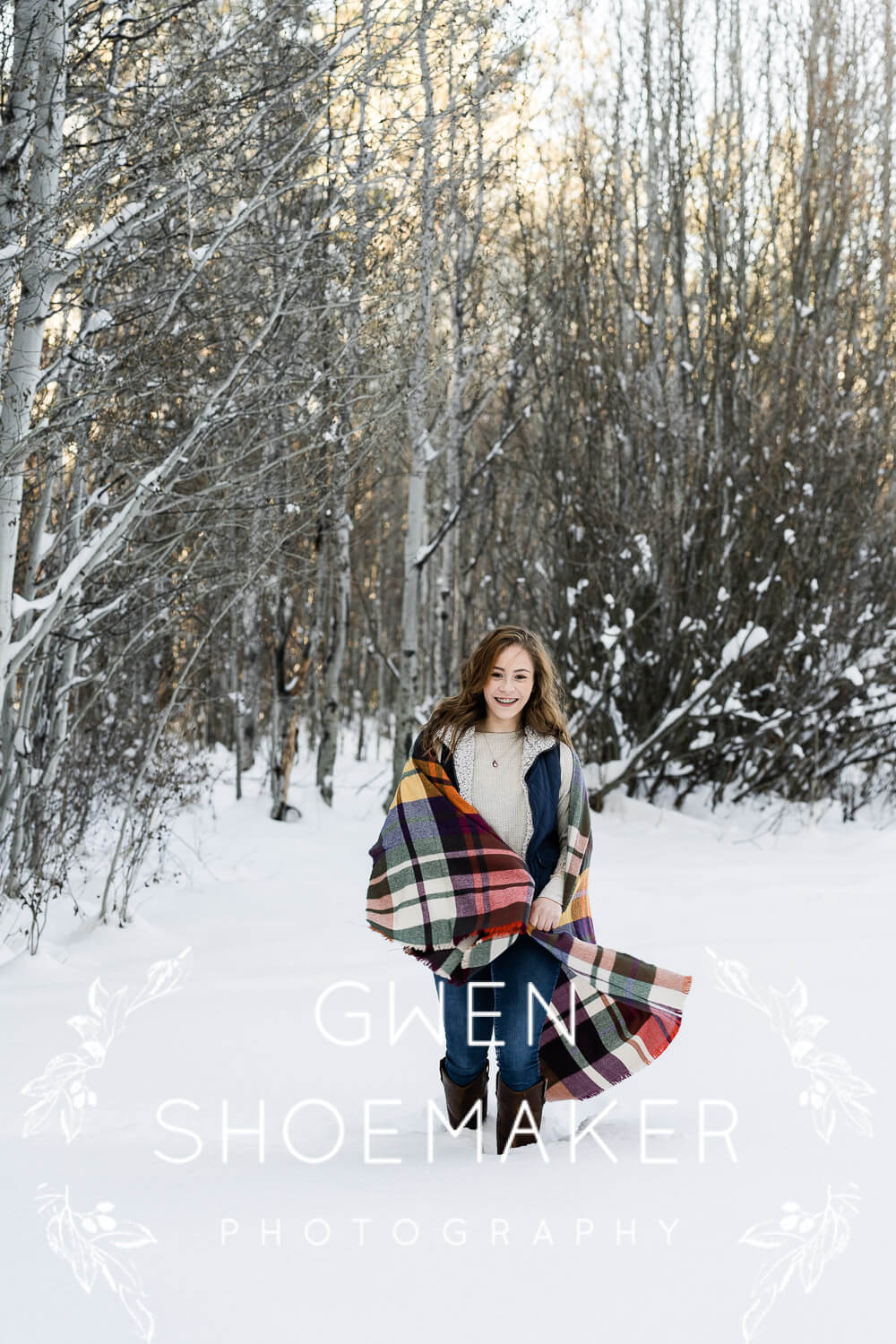 Senior girl walking in snow with colorful scarf.