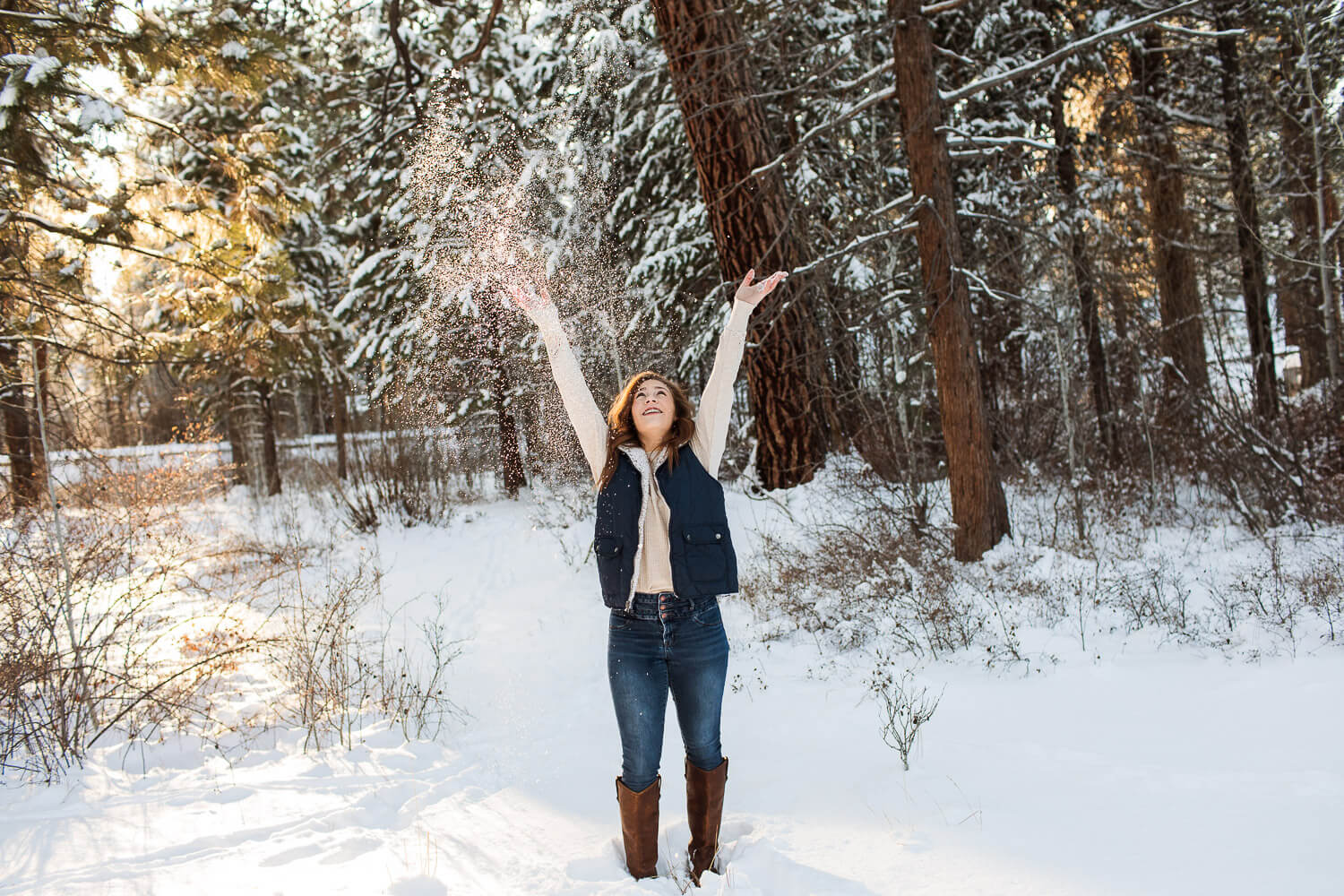 High school senior girl throwing snow in the air.