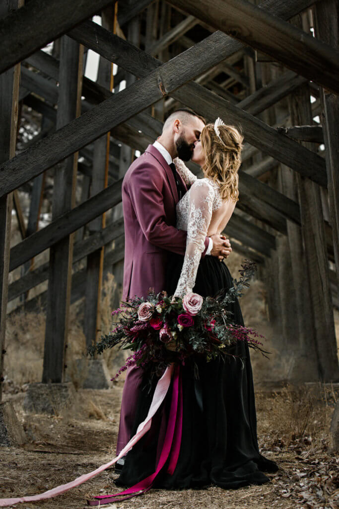 Modern couple kisses under the bridge at Brasada Ranch.