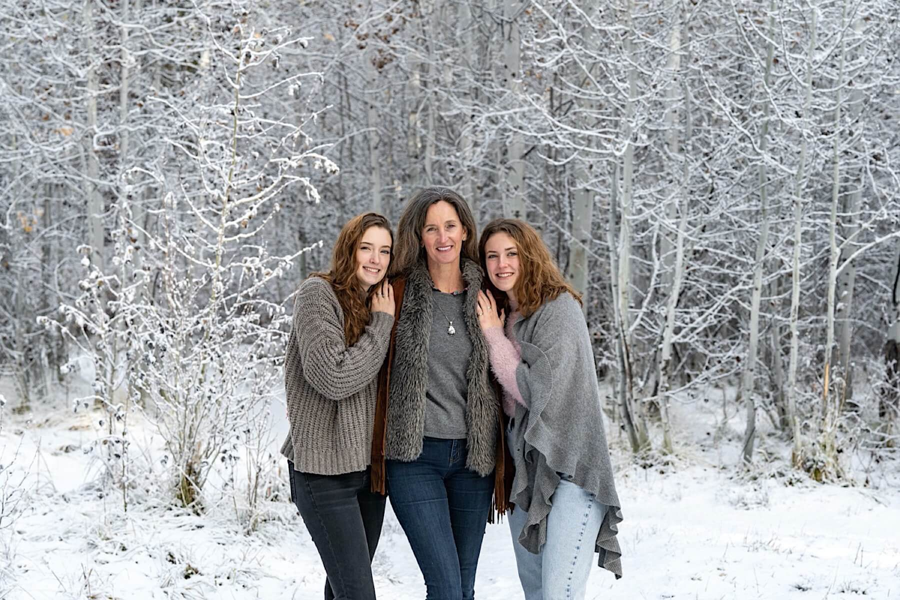 Daughter lean in and pose with mom. Background is white, frosty, snow covered aspen trees.