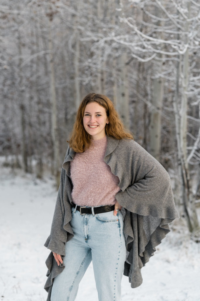 Girl in pink sweater and jeans in front of snowy landscape.
