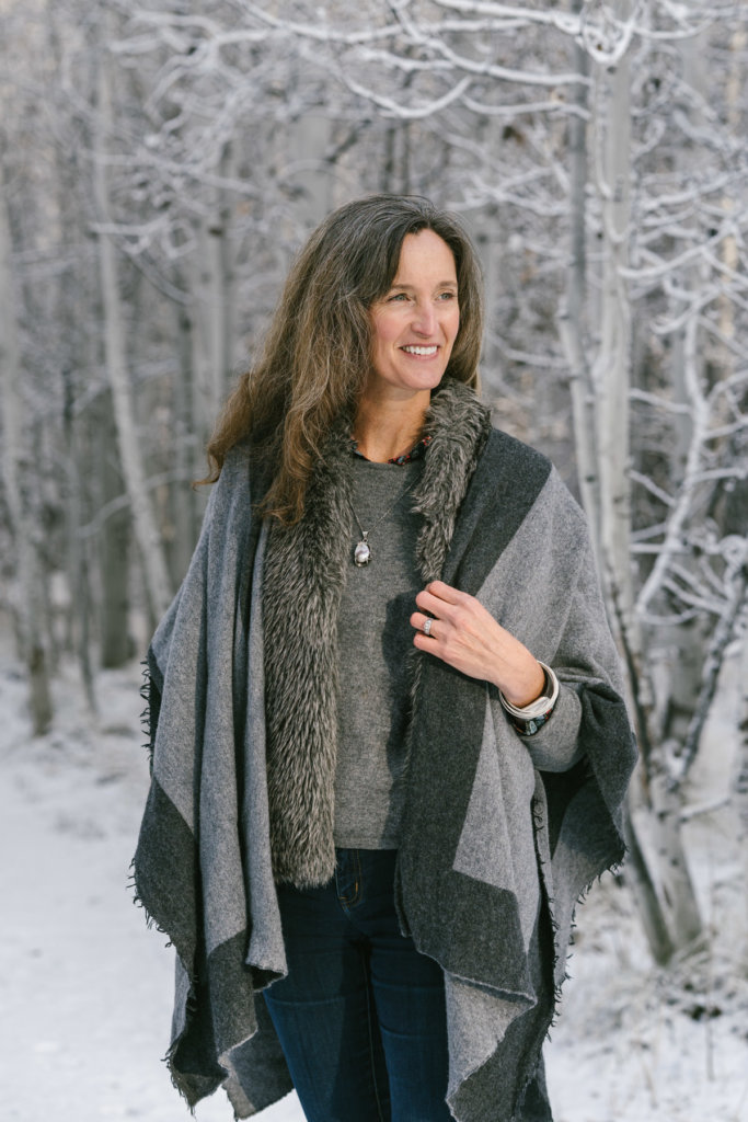 Woman wearing grey wool shawl in front of snowy trees.