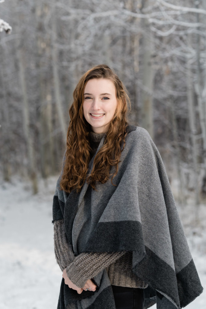 Portrait of daughter in front of snowy trees.