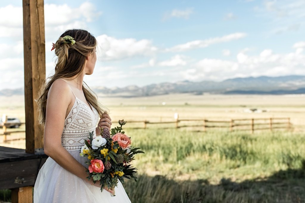 Bride looking towards the mountains across the sunny valley.