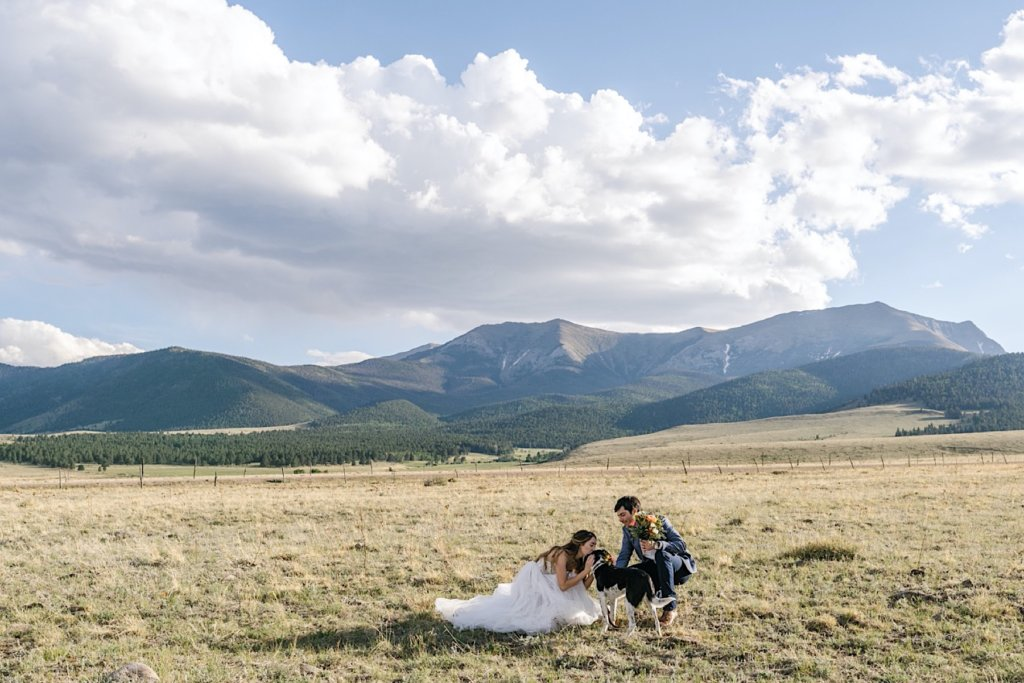 Bride and groom with their dog, mountains in the distance.