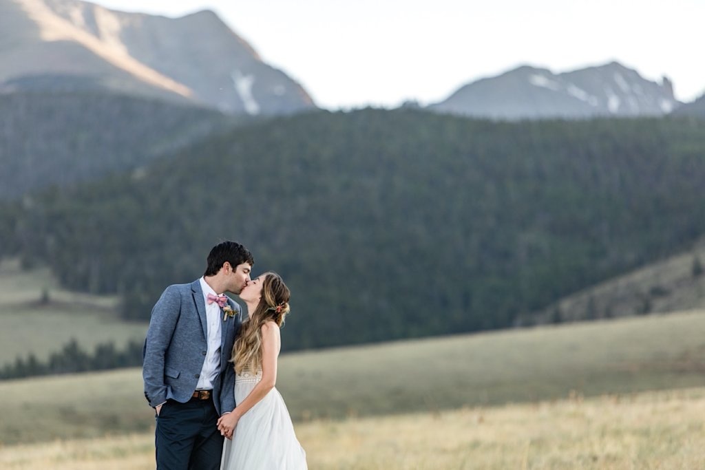 Newly weds kissing with the mountains in the background.