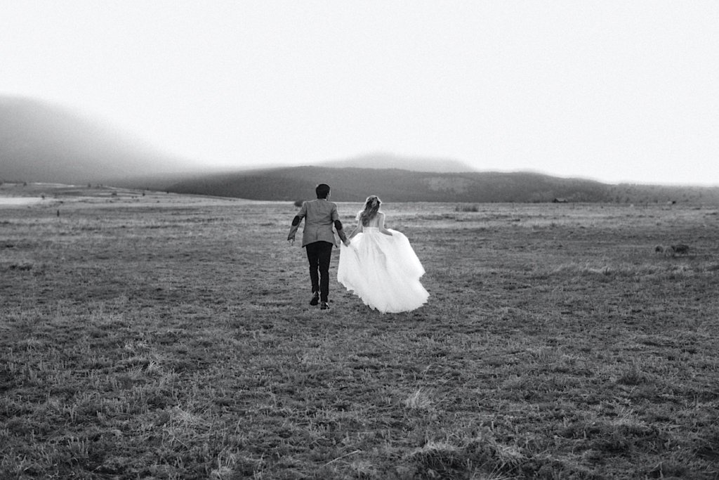 Black and white image of the couple running away from the camera.