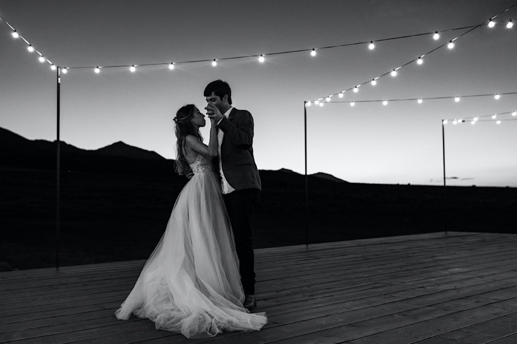 Black and white couple dancing on open air deck with tea lights.