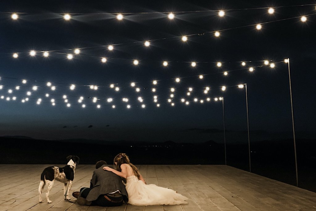 Tea lights strung across open air deck, the couple sits on the ground signing their wedding license with their dog.